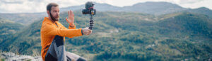 Influencer filming himself with a video camera while sitting atop a mountain overlooking a small town.