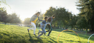 A family playing in a park with hula hoops.